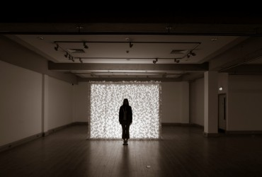 Artist Katie Moore in front of the illuminated Paper Bloom Exhibition