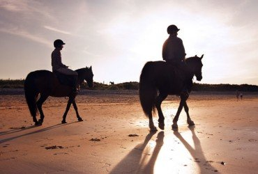 Horse-riding in Mayo - two riders on a beach at sunset
