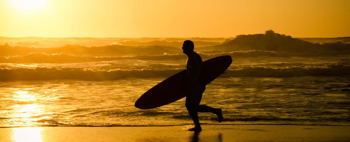 watersports in Mayo surfer running Enniscrone beach