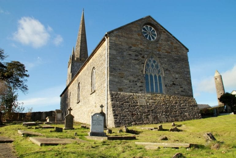 A view of Killala's 17th century cathedral with the 12th century round tower to the right and the souterrain entrance in the foreground.