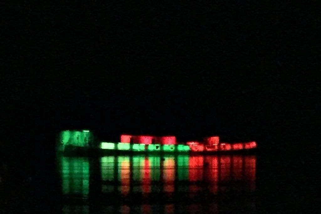 Creteboom Ballina concrete ship lit at night in green and red