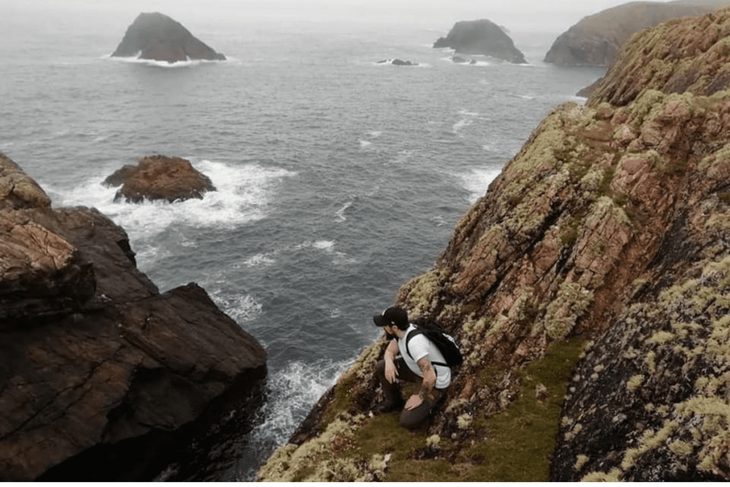 Person stopping to admire the views of the coastline on the Erris Head Loop Walk, Belmullet, North Mayo